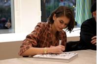 For a book signing during PFW, Kaia opted for a checkered suit look and a side-part Gen Z would not approve of.