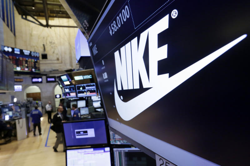 FILE - In this March 22, 2017, file photo, the Nike logo appears above the post where it trades on the floor of the New York Stock Exchange. Nike lost $790 million in the fourth quarter, as soaring digital sales couldn't make up for the loss of revenue from shuttered stores in most of the world. The world's largest sports apparel maker said Thursday, June 25, 2020, that its revenue fell 38% to $6.3 billion in the three-month period ending May 31. (AP Photo/Richard Drew, File)