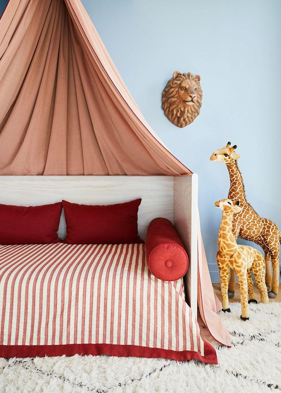 <p>What better place to look for nursery inspiration then a retro circus? Hang a little tent-like canopy over a daybed, opt for red and cream striped textiles, and pile on some throw and bolster pillows. Then pack in the animal motifs. Today, the daybed can be used as a comfy place for late-night feedings, but one day it'll be a big-kid bed—stylish, ageless, multi-purpose furniture is always a good investment.</p>