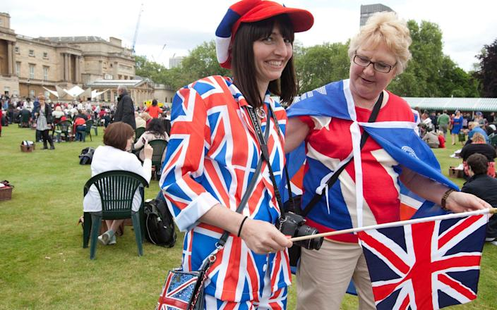 Picnic goers wearing Union Jacks as they enjoy a special picnic in the grounds of Buckingham Palace, ahead of the Diamond Jubilee in 2012 - Getty Images