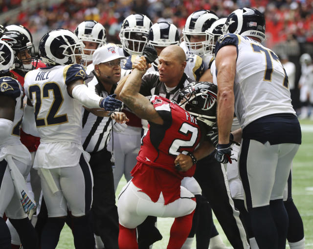 Officials restrain Atlanta Falcons running back Devonta Freeman (24) during a fight between the Falcons and the Los Angeles Rams during the second half of an NFL football game on Sunday, Oct. 20, 2019, in Atlanta. (Curtis Compton/Atlanta Journal-Constitution via AP)
