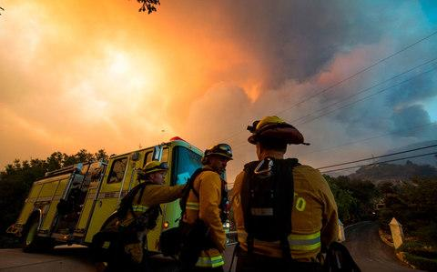 Firefighters from the Governors Office of Emergency Services monitor the advance of smoke and flames from the Thomas Fire in Montecito - Credit: AFP