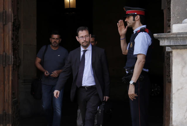 A Mosso D'Esquadra (Catalan regional police officer) salutes Spanish anti-corruption prosecutor Jose Grinda Gonzalez (2R) as he leaves the Generalitat (Catalan Government) in Barcelona on July 20, 2017. (PAU BARRENA/AFP/Getty Images)