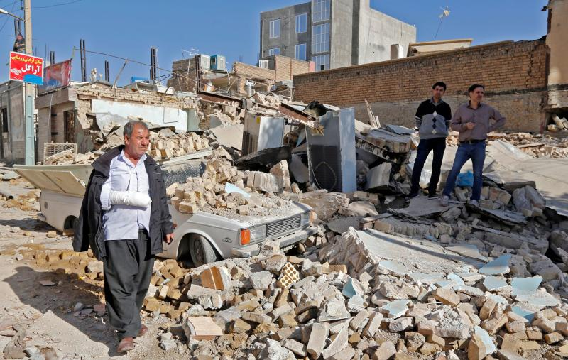 An injured Iranian walks through rubble in Sarpol-e Zahab, a town in Iran's western Kermanshah Province, on Tuesday. (ATTA KENARE via Getty Images)