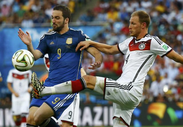Argentina's Gonzalo Higuain fights for the ball with Germany's Benedikt Hoewedes (R) during their 2014 World Cup final at the Maracana stadium in Rio de Janeiro July 13, 2014. REUTERS/Kai Pfaffenbach (BRAZIL - Tags: SOCCER SPORT WORLD CUP)