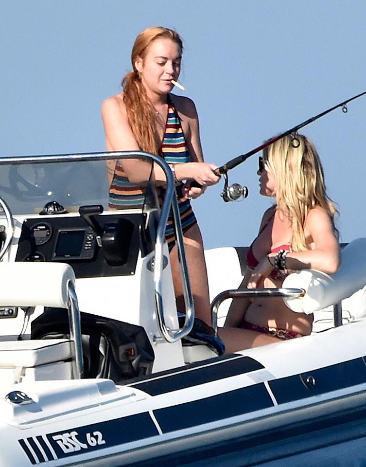 """Needless to say, the redhead is not your typical angler. Amid her <a href=""""https://www.yahoo.com/celebrity/the-next-stage-of-lindsay-1480493155582006.html"""">relationship drama</a> with fiancé Egor Tarabasov, she cleared her head out in the water, off the shores of Sardinia, Italy. No yellow raincoat for her though. She rolled with a striped swimsuit and cigarette. <i>(Photo: AKM-GSI)</i><br />"""