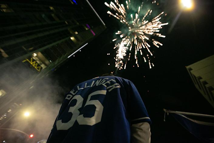 A person in a Cody Bellinger jersey is seen with fireworks exploding in the sky overhead.