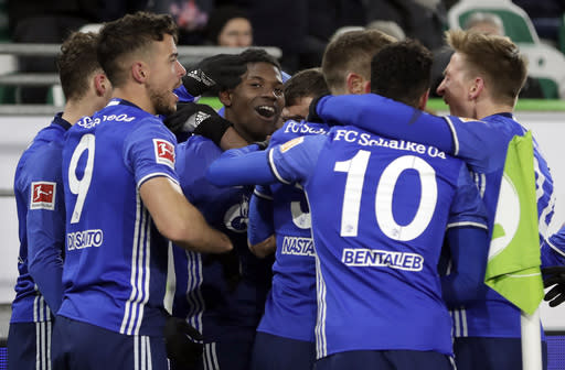 Schalke's Breel Embolo, center, and his teammates celebrate an own goal scored by Wolfsburg's Robin Knoche during the German Bundesliga soccer match between VfL Wolfsburg and FC Schalke 04 in Wolfsburg, Germany, Saturday, March 17, 2018. (AP Photo/Michael Sohn)