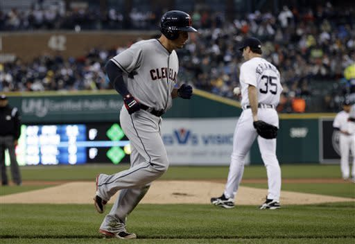 Cleveland Indians' Asdrubal Cabrera, foreground, scores on a Jason Giambi walk with the bases loaded against Detroit Tigers pitcher Justin Verlander (35)in the first inning of a baseball game in Detroit, Saturday, May 11, 2013. (AP Photo/Paul Sancya)