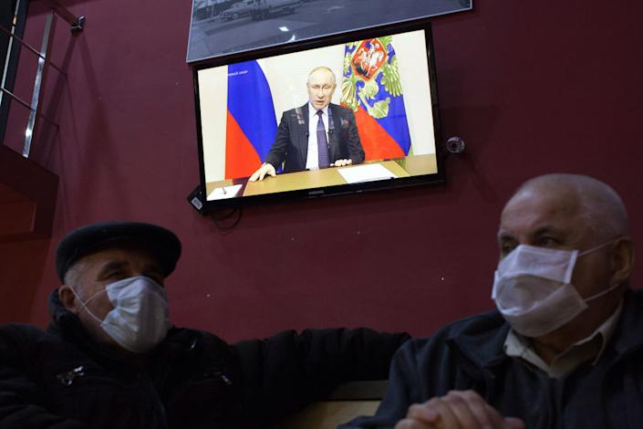 Customers wear protective face masks inside a cafe as a television screen displays Vladimir Putin, Russia's president, delivering a national address, in Moscow, Russia, on Wednesday, March 25, 2020. | Andrey Rudakov —Bloomberg via Getty Images