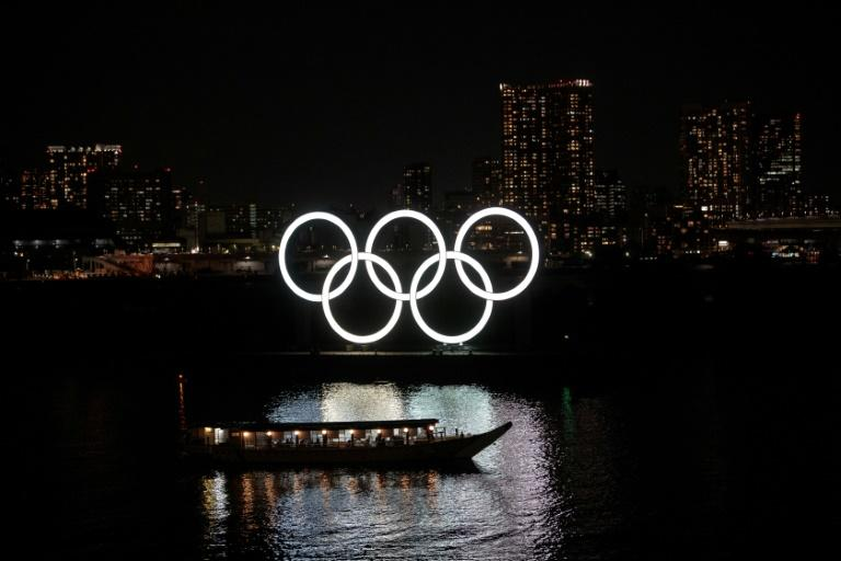 The Olympic rings are seen at night in Tokyo