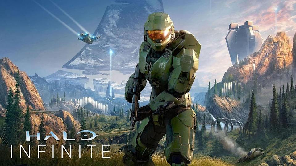 Master Chief stands in the center of the image brandishing a blaster rifle, as the familiar sights and landscape of the planet Halo surrounds him.