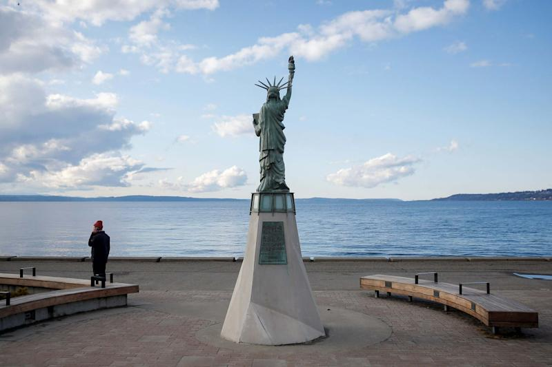A man talks on the phone near the Statue of Liberty replica at a mostly empty Alki Beach Park in Seattle, Washington, U.S. March 25, 2020: REUTERS