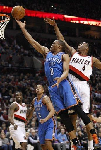 Oklahoma City Thunder's Russell Westbrook (0) lays the ball up as Portland Trail Blazers' Nolan Smith (4) defends in the first quarter during an NBA basketball game, Tuesday, March 27, 2012, in Portland, Ore. (AP Photo/Rick Bowmer)
