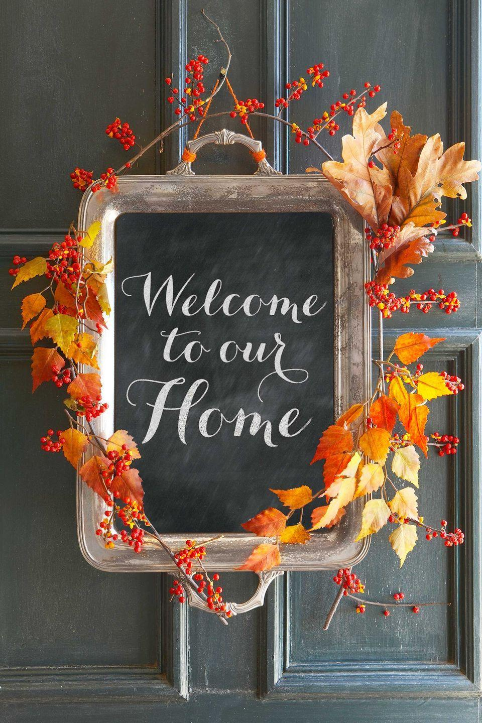 <p>Greet guests with this charming alternative to a fall wreath. Simply apply a layer of chalkboard paint to the inside of an old tray, then add autumn leaves and bittersweet berries for a seasonal finish. (Swap in evergreen and holly for the holidays!)</p>