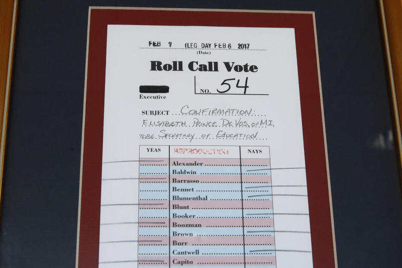 In this Aug. 9, 2017, photo, a framed reproduction of the roll call vote in Congress to approve Betsy DeVos as education secretary hangs on a wall in her office at the Education Department in Washington. It's been six months since her bruising Senate confirmation battle, and DeVos remains highly divisive. (AP Photo/Jacquelyn Martin)