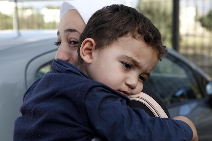 """Bushr Al Tawashi, as he is carried by his mother Arin Al Dakkar, outside of a private Sigma TV station, in Nicosia, Cyprus, Friday, Oct. 26, 2012. A 2-year-old Syrian boy who was believed dead after his family inadvertently left him behind as they fled shelling in Damascus last summer has been reunited with his parents in Cyprus, a lawyer said. """"You can imagine how they felt when they were told their son was alive after bearing all this guilt thinking that he was dead,"""" lawyer Stella Constantinou told The Associated Press. (AP Photo/Petros Karadjias)"""