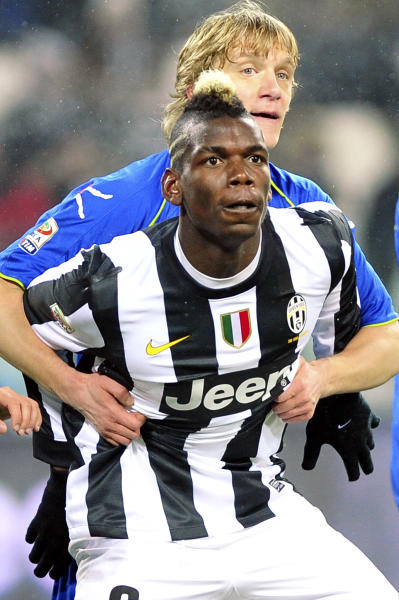 Juventus' Paul Pogba, of France, foreground, and Udinese's Dusan Basta keep their eyes on the ball, during a Serie A soccer match at the Juventus Stadium in Turin, Italy, Saturday, Jan. 19, 2013. (AP Photo/Massimo Pinca)