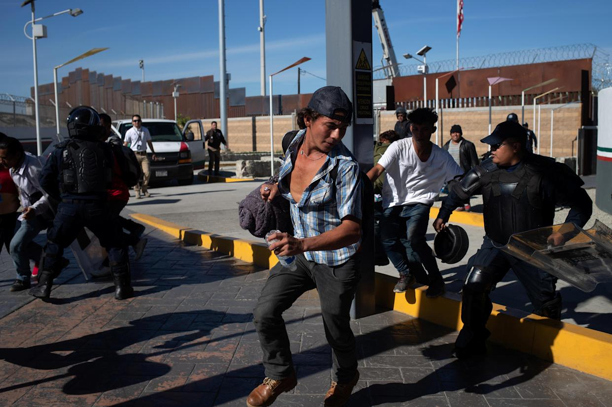 Mexico's Federal Police try to detain migrants, part of a caravan of thousands from Central America, as they attempt to cross the border into the United States from Tijuana, Mexico November 25, 2018. (Photo: Adrees Latif/Reuters)
