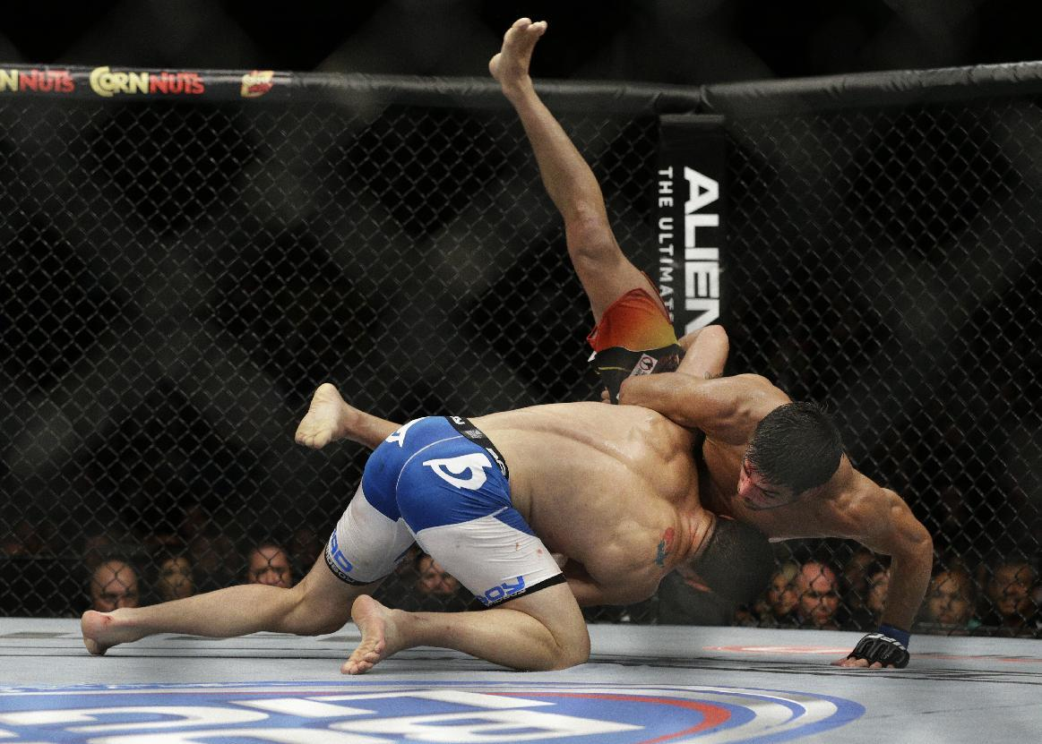 Chris Weidman, left, takes down Lyoto Machida during their mixed martial arts middleweight title bout at UFC 175 Saturday, July 5, 2014, in Las Vegas. (AP Photo/John Locher)