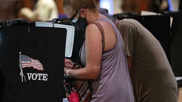 PHOTO: Voters fill out their ballots as they vote at the Stephen P. Clark Government Center polling station, Oct. 21, 2020, in Miami. (Joe Raedle/Getty Images)