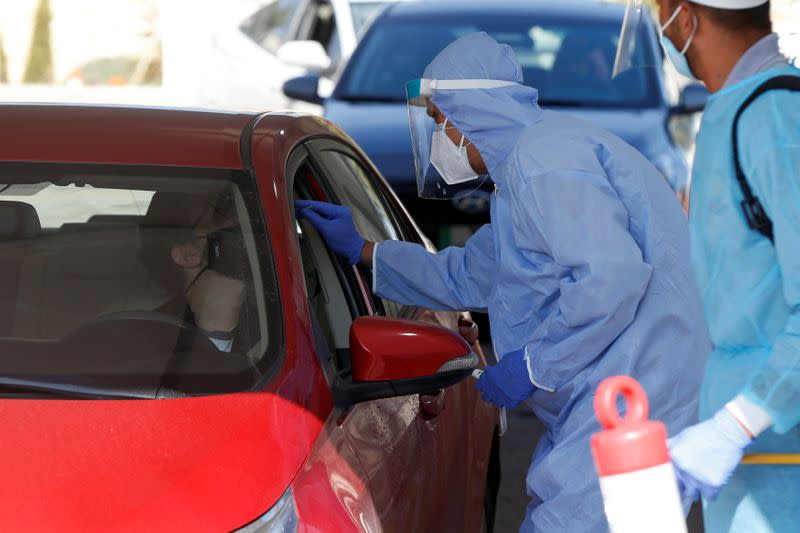 Healthcare worker takes nasal swab samples to check for the coronavirus disease (COVID-19) at a drive-thru testing station in Amman