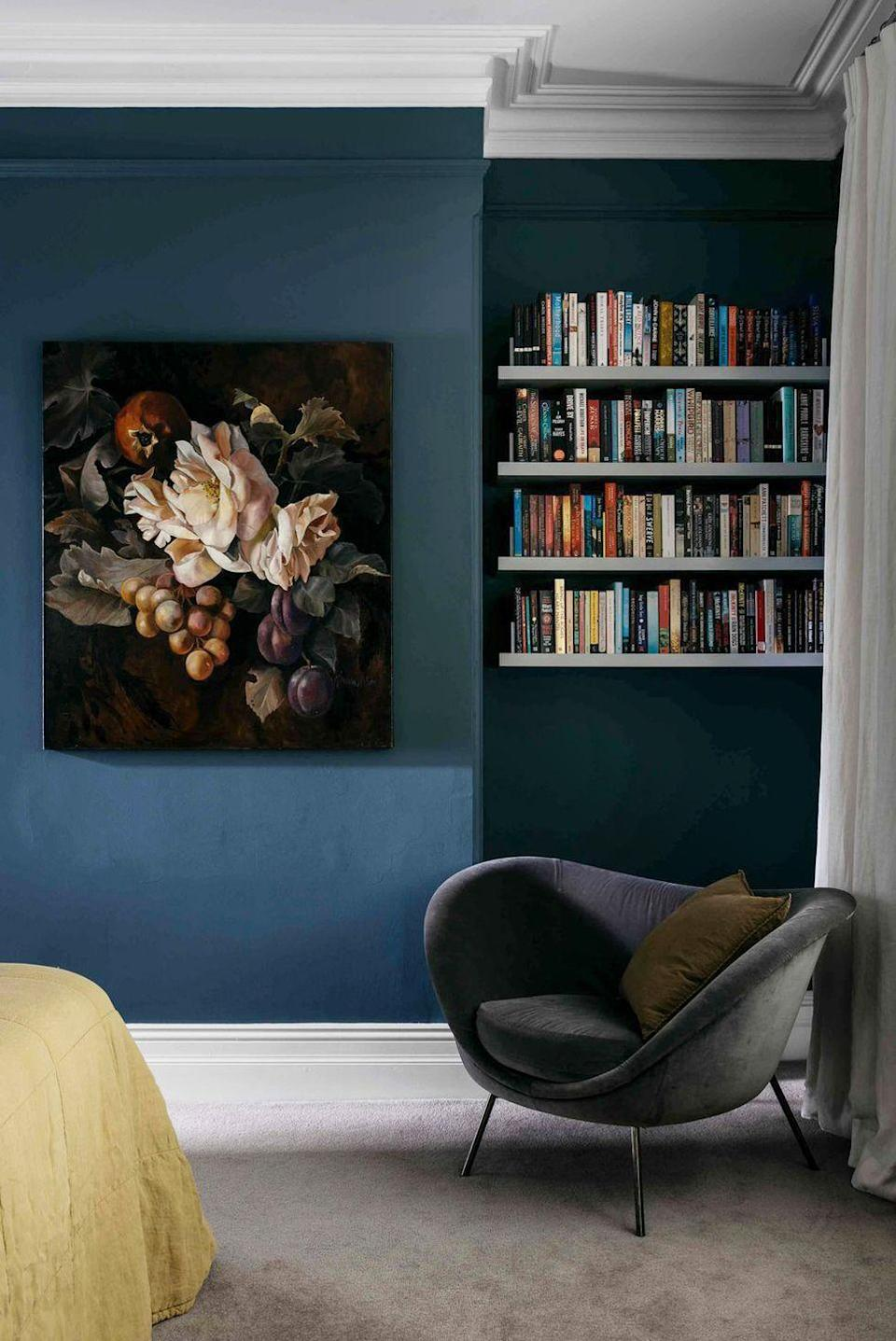 """<p>Create a cozy corner reading nook in your bedroom with a dark paint color, plush fabrics, emotive artwork, and of course, easy-to-reach books. In this bedroom designed by <a href=""""http://arentpyke.com/"""" rel=""""nofollow noopener"""" target=""""_blank"""" data-ylk=""""slk:Arent & Pyke"""" class=""""link rapid-noclick-resp"""">Arent & Pyke</a>, the rows of floating shelves provide a home for the occupant's collection. </p>"""