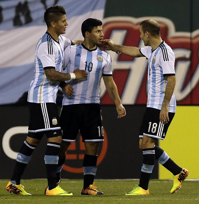 Argentina's Sergio Aguero, center, is congratulated by teammates Marcos Rojo, left, and Rodrigo Palacio after scoring during the second half of an international friendly soccer match against Bosnia Monday, Nov. 18, 2013, in St. Louis. Argentina won 2-0. (AP Photo/Jeff Roberson)