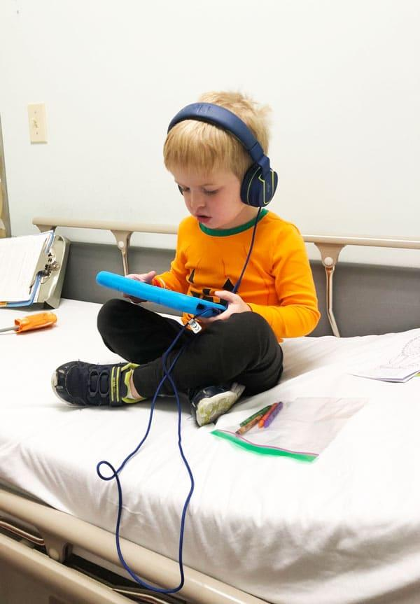 My Son Has Eosinophilic Esophagitis: little boy laying in bed on tablet