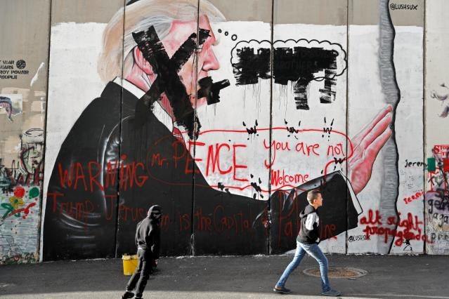 <p>Palestinian children walk past vandalised graffiti depicting President Donald Trump and slogans against Vice President Mike Pence painted on Israel's controversial separation barrier in the West Bank city of Bethlehem during clashes with Palestinian protestors near an Israeli checkpoint on Dec. 7, 2017. (Photo: Thomas Coex/AFP/Getty Images) </p>