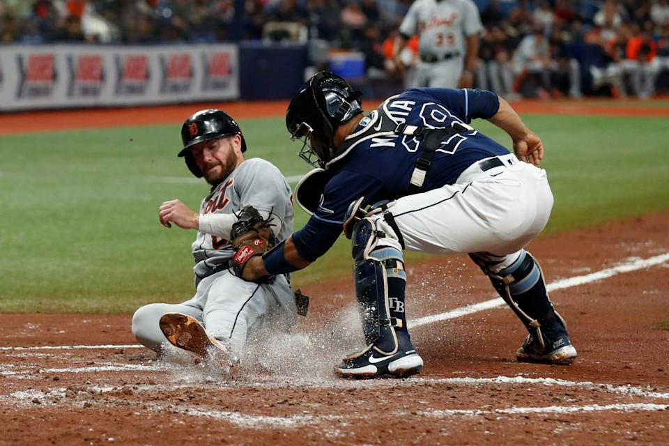 Detroit Tigers' Robbie Grossman, left, beats the tag of Tampa Bay Rays catcher Francisco Mejia while sliding safely home during the third inning of a baseball game Friday, Sept. 17, 2021, in St. Petersburg, Fla.