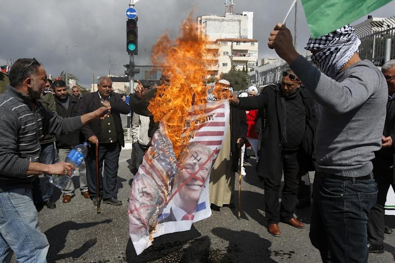 Palestinians burn images of Israeli Prime Minister Benjamin Netanyahu and US President Donald Trump in protest at Israel's decision to withhold Palestinian tax receipts that has helped trigger a suffocating financial crisis (AFP Photo/Musa Al SHAER)