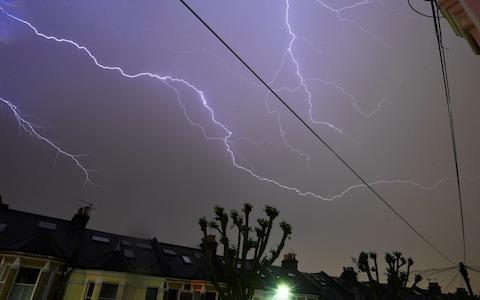 Lightning is seen from a bedroom window - Credit: REUTERS/Dylan Martinez