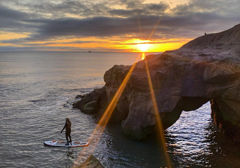 Anna Heslop, 25, paddleboarding during sunrise at Cullercoats Bay on the North East coast. Picture date: Tuesday March 30, 2021. Temperatures in parts of the UK are expected to be significantly warmer this week as families and friends are reunited and sporting activities are allowed to resume in England.