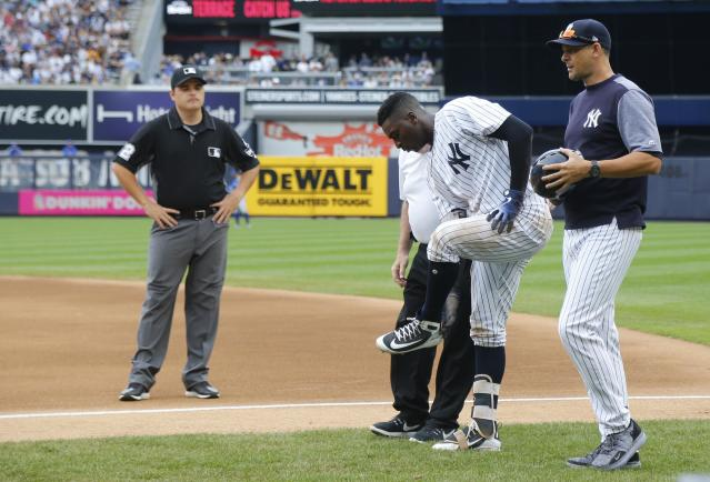 New York Yankees trainer Steve Donohue, third from right, and manager Aaron Boone, right, check on Didi Gregorius, second from right, after a collision with Toronto Blue Jays first baseman Kendrys Morales (not shown) in the first inning of a baseball game in New Yorkm, Sunday, Aug. 19, 2018. (AP Photo/Noah K. Murray)