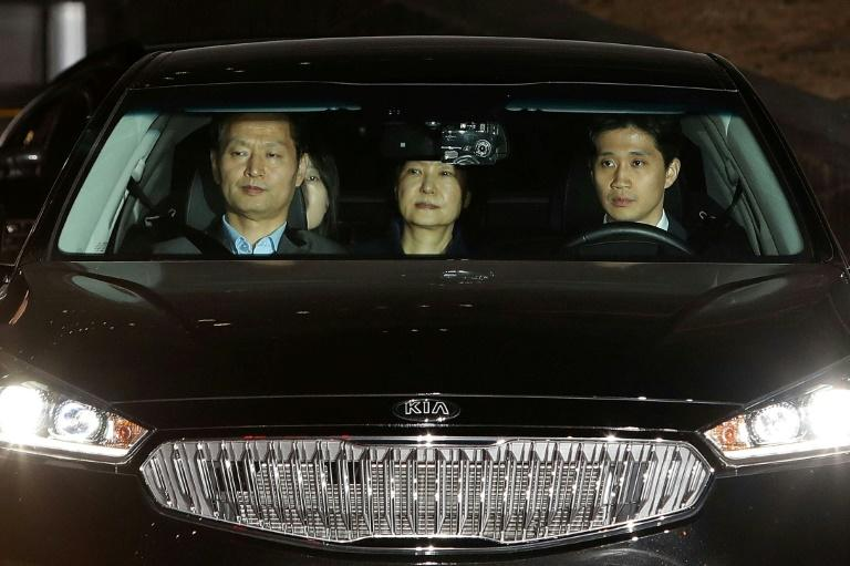 Ousted South Korean President Park Geun-hye (C), leaves the prosecutors' office in a car as she is transferred to a detention house early on March 31, 2017 in Seoul