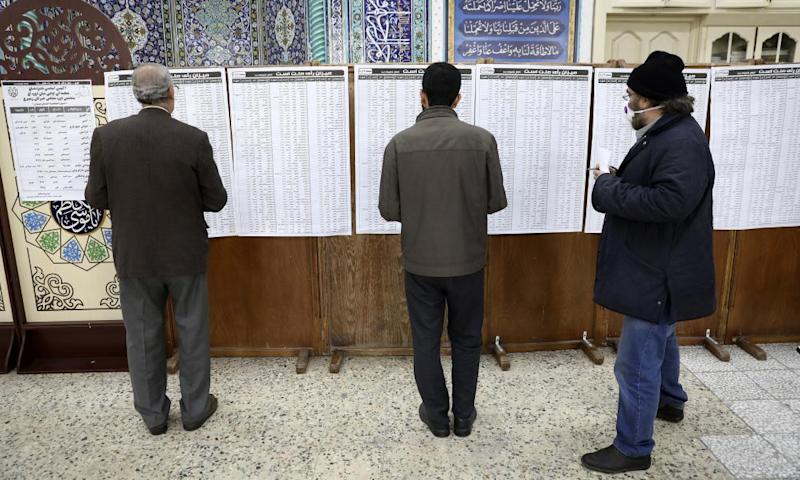 Voters check the dizzying list of the candidates at a polling station in Tehran.