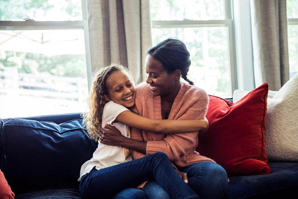 An image of a mom and daughter hugging on a couch.