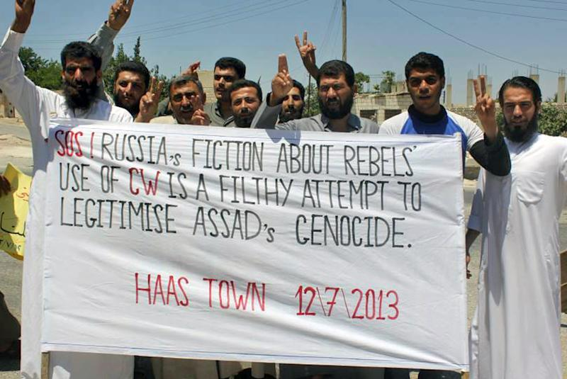 """In this citizen journalism image provided by Edlib News Network, ENN, which has been authenticated based on its contents and other AP reporting, anti-Syrian regime protesters hold a banner and flash the victory sign during a demonstration in Hass town, Idlib province, northern Syria, Friday, July 12, 2013. Syria's main opposition bloc complained that """"elements in the U.S. Congress"""" are obstructing the Obama administration's efforts to step up support for the rebels, as regime forces on Friday intensified their offensive on opposition strongholds. (AP Photo/Edlib News Network ENN)"""