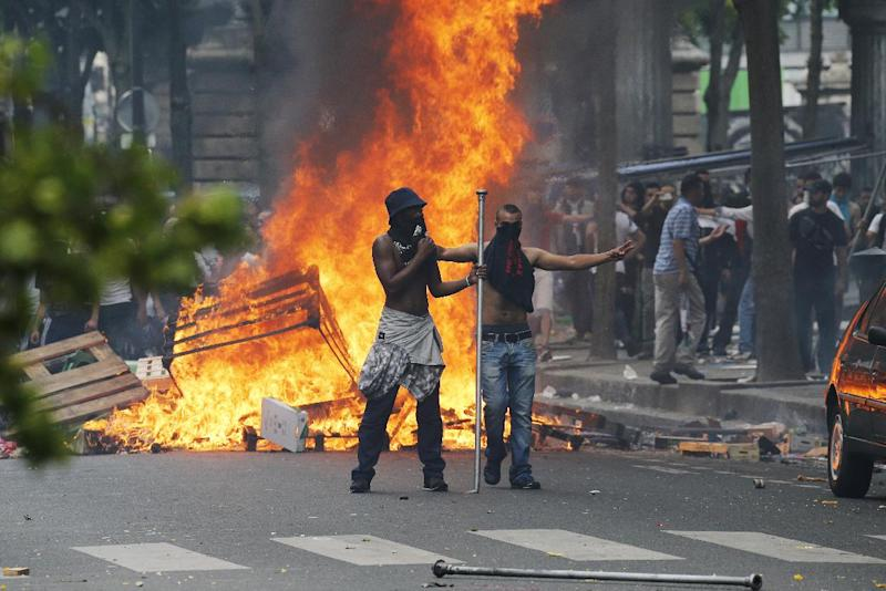 Demonstrators in front of a fire barricade near Barbes-Rochechouart Metro station, in Paris, on July 19, 2014 during clashes with French riot police in the aftermath of a demonstration, banned by police, to denounce Israel's military campaign in Gaza
