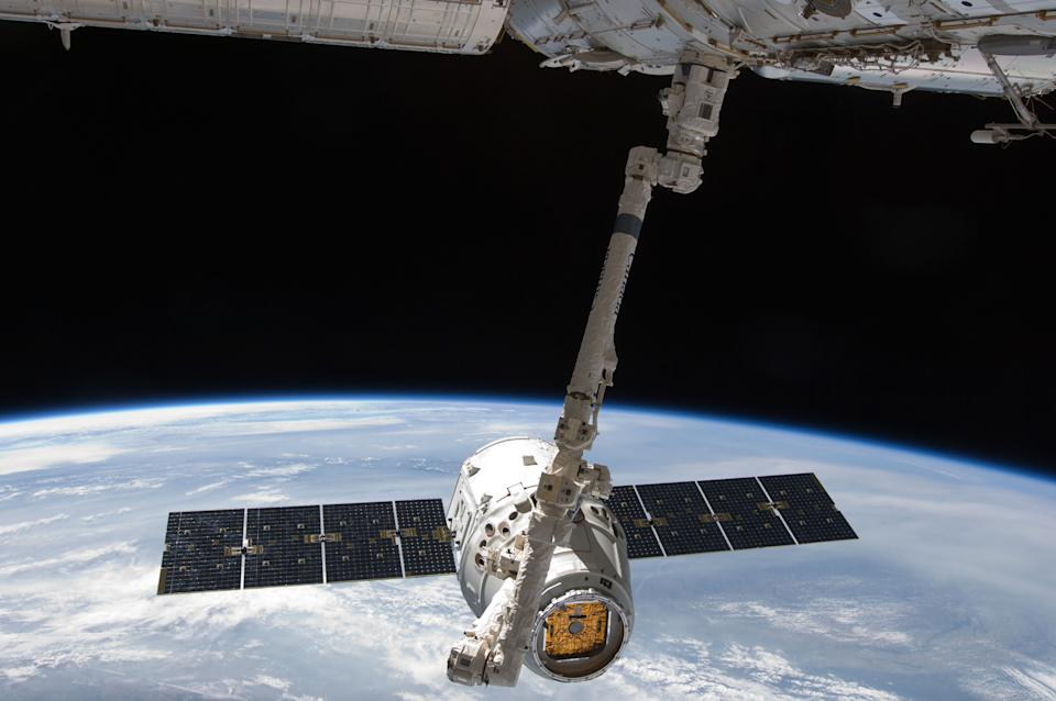 The SpaceX Dragon commercial cargo craft is grappled by the Canadarm2 robotic arm at the International Space Station in this May 25, 2012 NASA handout photo.  The capsule -- carrying 3,100 pounds of science samples and other equipment --  made a parachute splashdown into the Pacific Ocean May 21, 2015, wrapping up a five-week stay at the International Space Station. REUTERS/NASA/Handout via Reuters  - 427711a0 e4c2 11eb b3fd adb8d6067f76 - The billionaire space race could benefit regular people, too