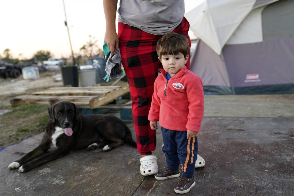 Katelyn Smith stands with her one year old son Ricky Trahan, III, as she prepares to change his clothes, as their family lives in a camper and tents where their home was destroyed, in the aftermath of Hurricane Laura and Hurricane Delta, in Lake Charles, La., Friday, Dec. 4, 2020. (AP Photo/Gerald Herbert)