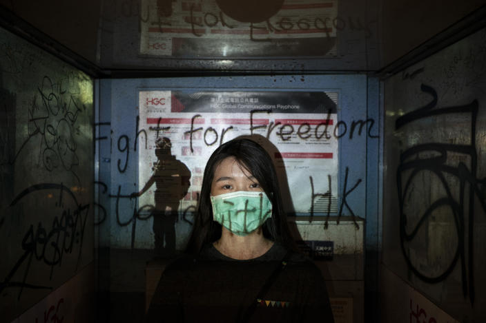 "A 24-year-old protester who identified herself as Josephine, poses for a portrait as a projector displays a photograph, previously taken during the unrest, over her at a protest in Hong Kong. Josephine said she is afraid of the mask law, ""but we are still coming out because we need to find hope, to find the future of Hong Kong."" (Photo: Felipe Dana/AP)"