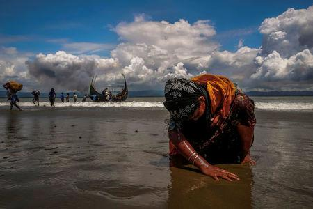 An exhausted Rohingya refugee woman touches the shore after crossing the Bangladesh-Myanmar border by boat through the Bay of Bengal, in Shah Porir Dwip, Bangladesh September 11, 2017. REUTERS/Danish Siddiqui