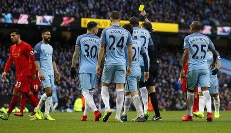 Manchester City's Gael Clichy is shown a yellow card by referee Michael Oliver after conceding a penalty