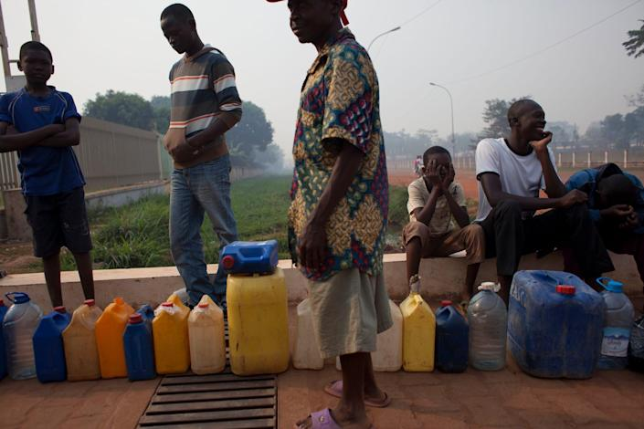 People waiting to purchase fuel hold their places in line with jerrycans at a gas station that was closed, as they await the arrival of military police, in Bangui, Central African Republic, Tuesday, Dec. 24, 2013. With few gas stations open and reliable fuel hard to find, people lined up as early as 4 a.m. at this station, which wasn't slated to open until police protection arrived around 9 or 10 a.m. (AP Photo/Rebecca Blackwell)