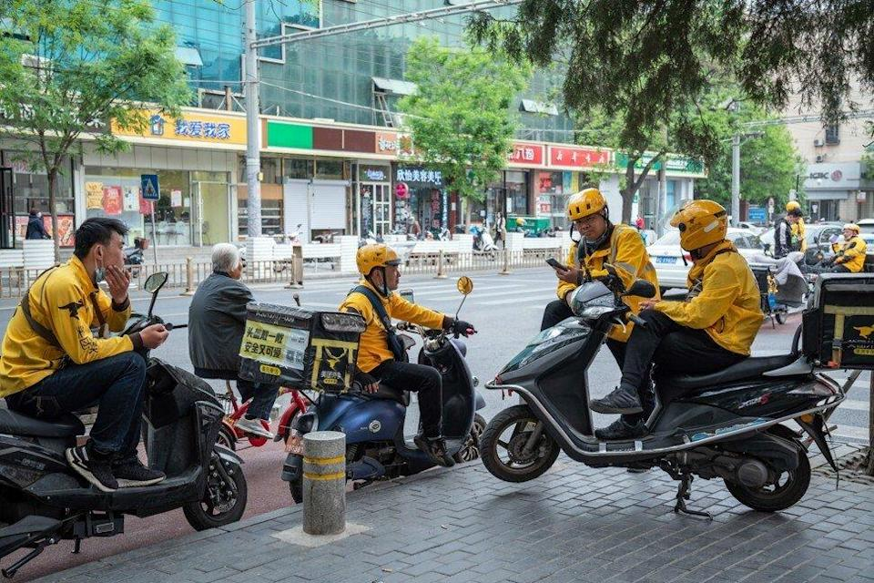 Food delivery couriers for Meituan gather around motorcycles in Beijing, China, on Wednesday, April 21, 2021. Photo: Bloomberg