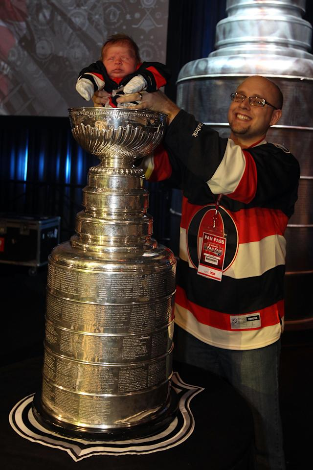 OTTAWA, ON - JANUARY 27: Jean Marc Gionet (R) holds his son Kaleo on the Stanley Cup during the NHL Fan Fair at the Ottawa Convention Centre on January 27, 2012 in Ottawa, Ontario, Canada. (Photo by Christian Petersen/Getty Images)
