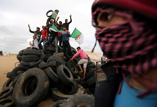 <p>Palestinian activists collect tyres to be burnt along the Israel-Gaza border, in the southern Gaza Strip, April 3, 2018. (Photo: Ibraheem Abu Mustafa/Reuters) </p>