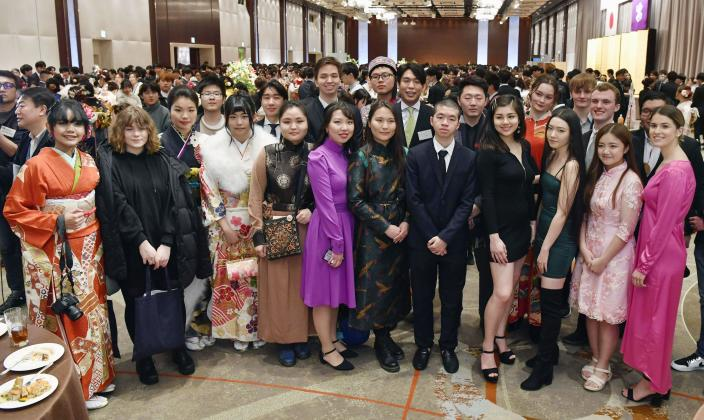 In this Jan. 13, 2020, photo, young foreigners, wearing ethnic clothes and kimonos, pose together for photographers as they attend a Coming-of-Age ceremony at Shinjuku district in Tokyo. In the district, one of Japan's most ethnically diverse town, more than 12 percent of its 348,000 residents are non-Japanese. On Monday, about half of some 4,000 people who celebrated coming of age at 20 were foreign residents.(Muneyuki Tomari/Kyodo News via AP)
